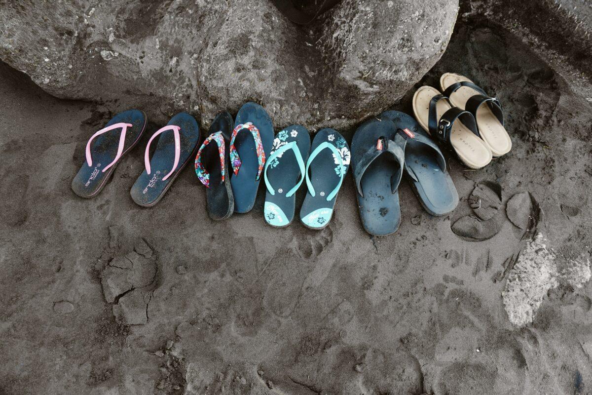Assorted flip flops on sand 952843